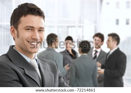 Smiling confident businessman portrait, group of businesspeople chatting in background.? - stock photo