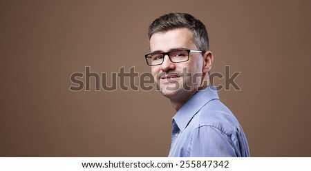Smiling confident businessman posing and looking at camera - stock photo