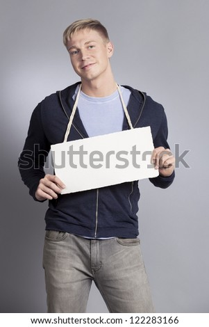 Smiling confident man presenting white blank signboard with space for text isolated on grey background. - stock photo