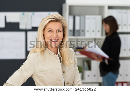 Smiling confident middle-aged businesswoman smiling at the camera as a colleague works in the background in the office - stock photo