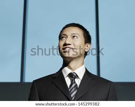Smiling confident young businessman looking up - stock photo