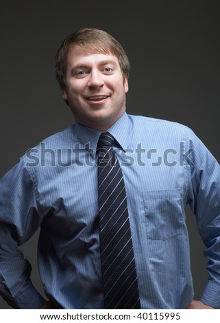 Smiling confident young businessman on dark background - stock photo