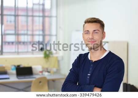 Smiling confident young businessman standing in the office looking at the camera with folded arms and a satisfied expression - stock photo