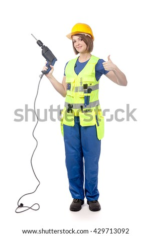 smiling construction female worker in yellow hardhat and reflective vest holding a drill and showing thumb up isolated on white background. proposing service. advertisement gesture