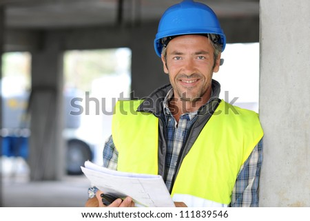 Smiling construction manager standing on building site - stock photo