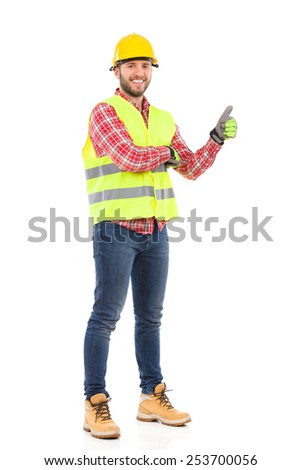 Smiling construction worker in yellow helmet and lime waistcoat showing thumb up. Full length studio shot isolated on white. - stock photo