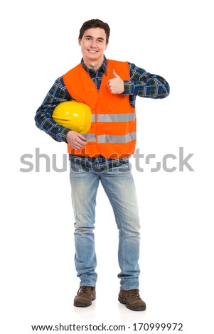 Smiling construction worker in yellow helmet and orange reflective waistcoat showing thumb up. Full length studio shot isolated on white. - stock photo