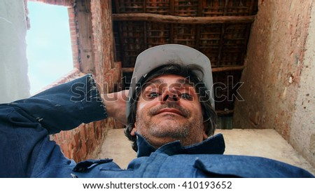 smiling Construction worker under a roof - stock photo