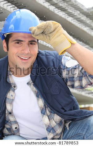 Smiling construction worker wearing a hardhat - stock photo