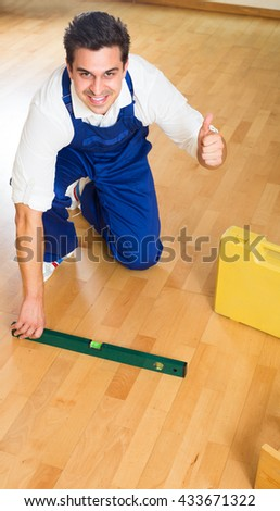 Smiling constructor fixing laminate flooring indoors