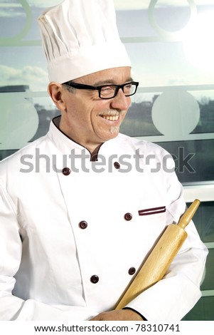 Smiling cook with white hat having pin roll in hand