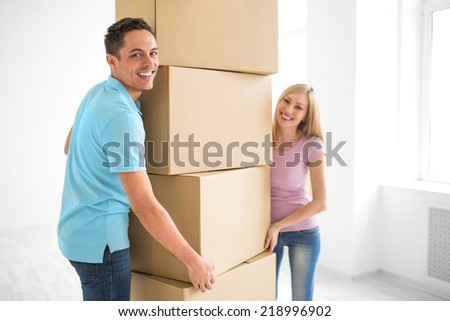 Smiling couple at home with boxes