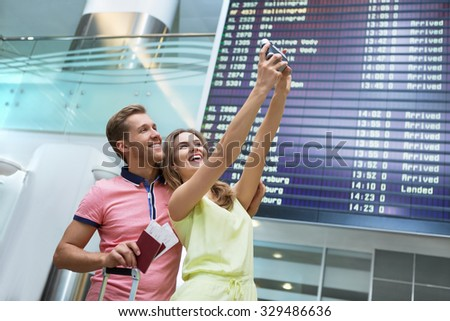 Smiling couple at the airport makes selfie - stock photo