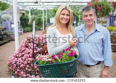Smiling couple buying plants holding a full basket in garden center