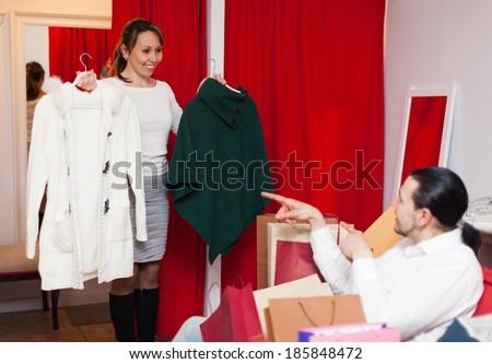 smiling couple choosing jacket at clothing store - stock photo