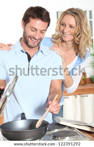 Smiling couple cooking - stock photo
