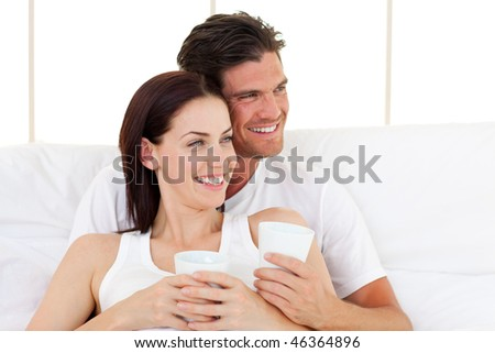 Smiling couple drinking coffee lying in the bed - stock photo