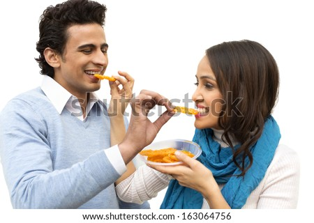 Smiling couple eating jalebis - stock photo