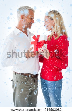 Smiling couple embracing and holding gift against snow falling - stock photo