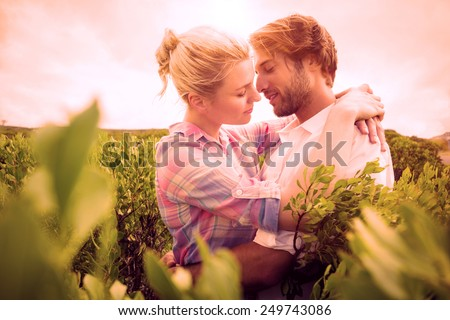 Smiling couple embracing outside among the bushes on a sunny day - stock photo