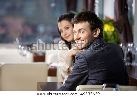 Smiling couple expect the order at restaurant - stock photo
