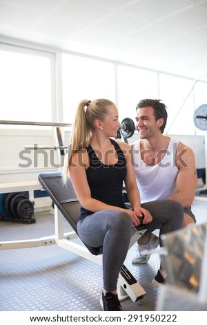 Smiling Couple Flirting with Each Other While Seated on Weight Bench in Brightly Lit Gym - stock photo
