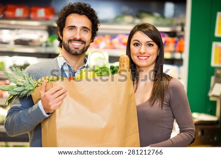 Smiling couple holding a shopping bag full of food in a supermarket - stock photo