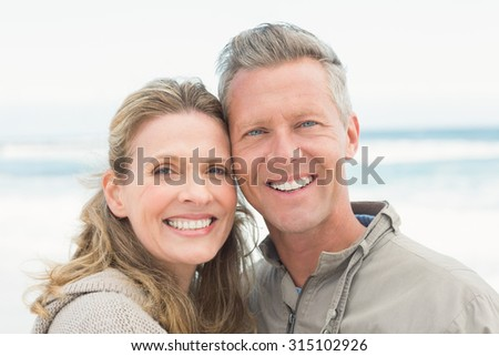 Smiling couple holding one another at the beach - stock photo