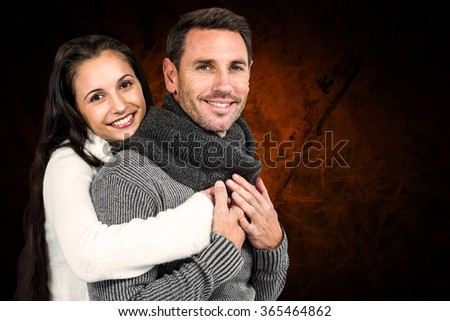 Smiling couple hugging and looking at camera against shades of brown - stock photo
