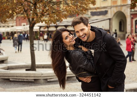 Smiling couple hugging each other in autumn scenery - stock photo