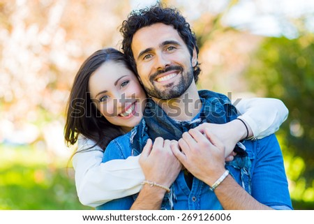Smiling couple hugging outdoor - stock photo