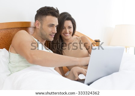 Smiling couple in bed with notebook - stock photo