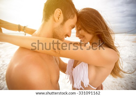 Smiling couple in love embracing and looking each other   - stock photo
