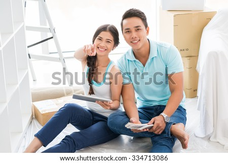 Smiling couple in their new flat pointing and smiling at camera - stock photo
