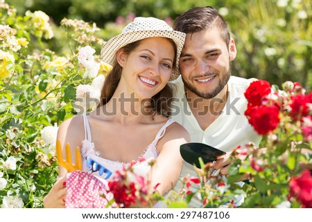Smiling couple is engaged in gardening together - stock photo