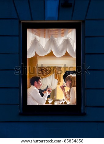 smiling couple is sitting at restaurant, view from street - stock photo