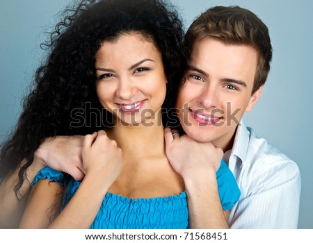 Smiling couple isolated on a greybackground - stock photo