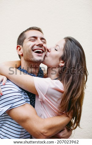 Smiling couple isolated on wall./ Beautiful young couple kissing. - stock photo