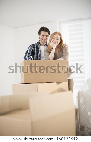 smiling couple leaning on boxes in new home - stock photo