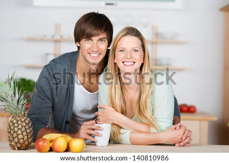 smiling couple leaning on the kitchen table - stock photo