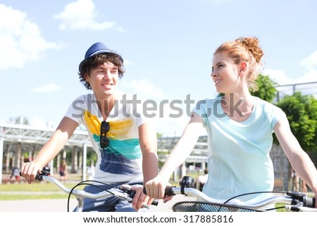 Smiling couple looking at each other while cycling in city - stock photo