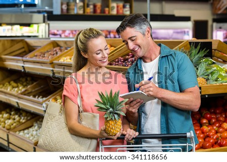 Smiling couple looking at the grocery list at the supermarket - stock photo
