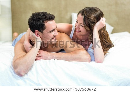 Smiling couple lying in bed together