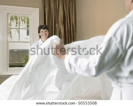 Smiling couple making bed together