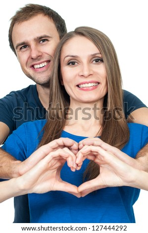 Smiling couple making heart gesture of love - stock photo