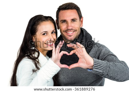 Smiling couple making heart shape with hands on white background - stock photo