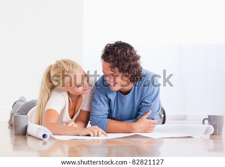 Smiling couple moving in a new house looking at a plan - stock photo