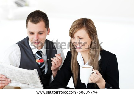 Smiling couple of businesspeople reading the newspaper drinking coffee in the morning