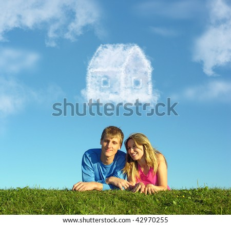 smiling couple on grass and dream cloud house collage - stock photo
