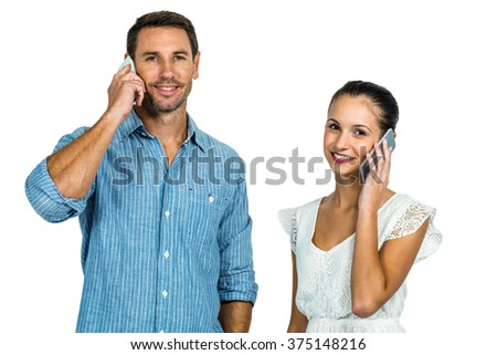 Smiling couple on phone call looking at the camera on white screen - stock photo